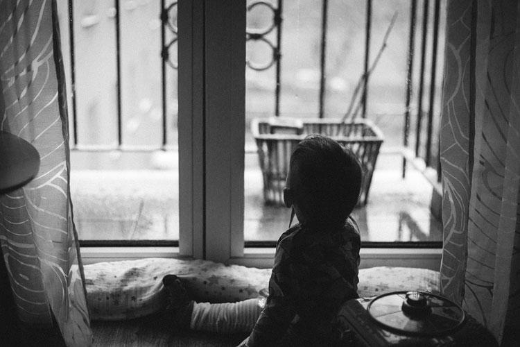 Mała dziewczynka wyglądająca przez okno w czasie kwarantanny. Zostań w domu